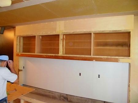 店内に戻ると既存の吊り戸棚のパテも仕上がり、こちらにもダイノックシートを貼り